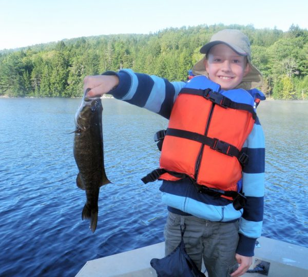 Kid holding a fish he caught on a lake in Maine - Northern Outdoors