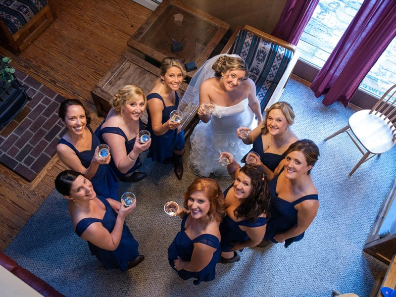 Bride and bridesmaids raising classes and toasting on the wedding day in western Maine