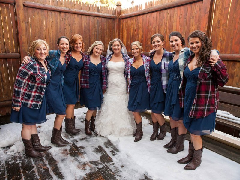 Bridal party in blue dresses and flannel shirts with cowboy boots - unique Maine winter wedding destination in The Forks