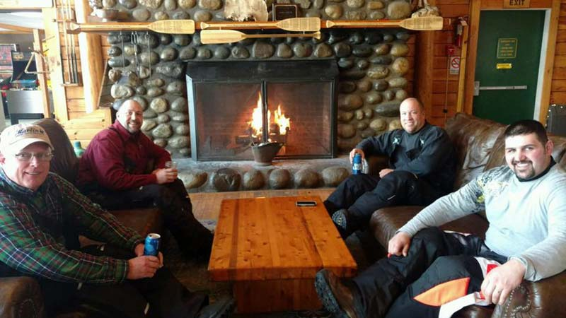 Snowmobilers having a Beer by the Fireplace