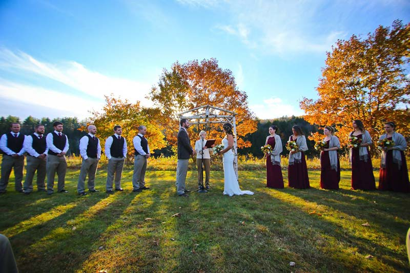 Maine wedding ceremony with full bridal party and blue sky with fall leaves