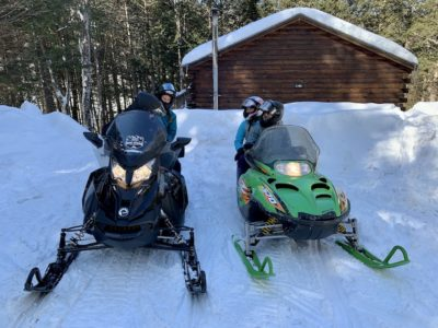 Couples Snowmobile from a Trailside Cabin